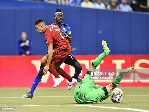 Goaltender Clint Irwin makes a save while Justin Morrow of the Toronto FC defends against Dominic Oduro of the Montreal Impact during leg one of the...