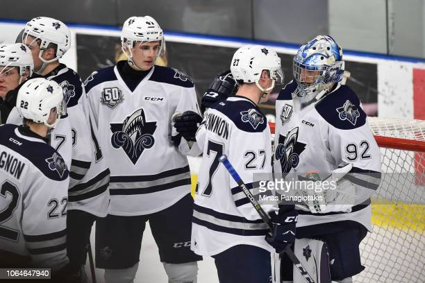 Goaltender Colten Ellis and teammate Carson MacKinnon of the Rimouski Oceanic celebrate their victory against the Blainville-Boisbriand Armada during...