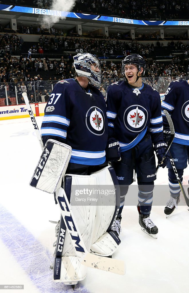 Goaltender Connor Hellebuyck #37 and Andrew Copp #9 of the Winnipeg Jets share a laugh as they leave the ice following a 2-1 victory over the Carolina Hurricanes at the Bell MTS Place on October 14, 2017 in Winnipeg, Manitoba, Canada.