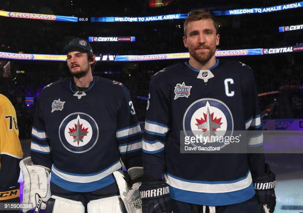 Goaltender Connor Hellebuyck and Blake Wheeler of the Winnipeg Jets stand on the ice before the 2018 GEICO NHL AllStar Skills Competition at Amalie...