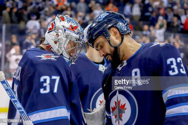 Goaltender Connor Hellebuyck and Dustin Byfuglien of the Winnipeg Jets celebrate following a 71 victory over the Philadelphia Flyers at the Bell MTS...