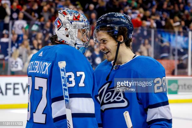 Goaltender Connor Hellebuyck and Jack Roslovic of the Winnipeg Jets celebrate following a 21 victory over the Calgary Flames at the Bell MTS Place on...