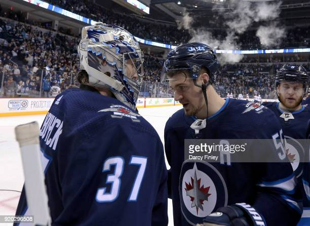Goaltender Connor Hellebuyck and Mark Scheifele of the Winnipeg Jets celebrate following a 72 victory over the Florida Panthers at the Bell MTS Place...