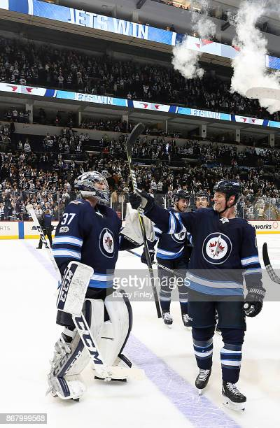 Goaltender Connor Hellebuyck and Matt Hendricks of the Winnipeg Jets celebrate as they leave the ice following a 71 victory over the Pittsburgh...