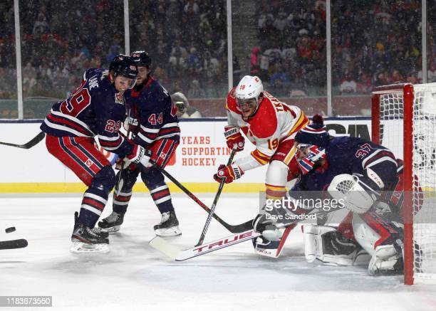 Goaltender Connor Hellebuyck and Patrik Laine of the Winnipeg Jets defend their net against Matthew Tkachuk of the Calgary Flames during the first...