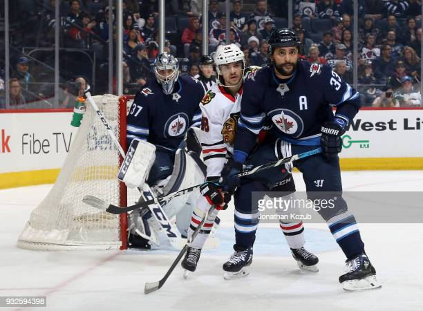 Goaltender Connor Hellebuyck Dustin Byfuglien of the Winnipeg Jets and Vinnie Hinostroza of the Chicago Blackhawks keep their eyes on the play along...