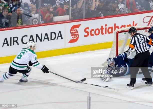 Goaltender Connor Hellebuyck of the Winnipeg Jets and Julius Honka of the Dallas Stars reach for the loose puck during second period action at the...