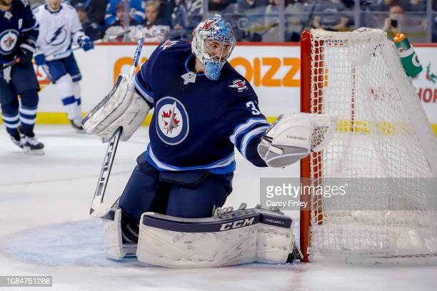 Goaltender Connor Hellebuyck of the Winnipeg Jets catches the puck in his glove during third period action against the Tampa Bay Lightning at the...
