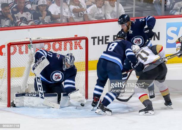 Goaltender Connor Hellebuyck of the Winnipeg Jets catches the puck in the crease as teammates Patrik Laine and Jacob Trouba defend against William...