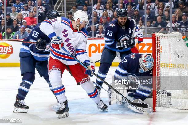 Goaltender Connor Hellebuyck of the Winnipeg Jets covers up the puck in the crease as Kevin Hayes of the New York Rangers looks for a rebound during...