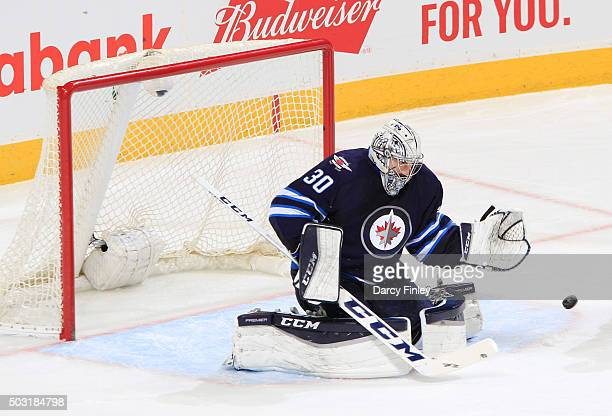 Goaltender Connor Hellebuyck of the Winnipeg Jets deflects the puck away from the net during second period action against the Pittsburgh Penguins at...