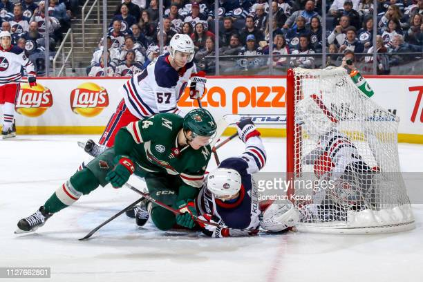 Goaltender Connor Hellebuyck of the Winnipeg Jets falls into the net as Joel Eriksson Ek of the Minnesota Wild jams the puck in for a third period...