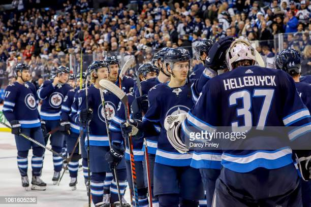 Goaltender Connor Hellebuyck of the Winnipeg Jets gets congratulated by teammates after backstopping the Jets to a 31 victory over the Washington...