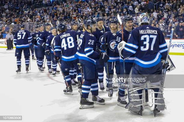 Goaltender Connor Hellebuyck of the Winnipeg Jets gets congratulated by teammates following a 71 victory over the Philadelphia Flyers at the Bell MTS...