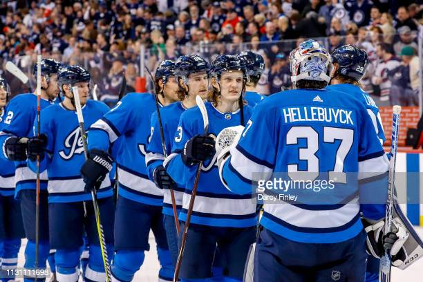 Goaltender Connor Hellebuyck of the Winnipeg Jets gets congratulated by teammates following a 21 victory over the Calgary Flames at the Bell MTS...