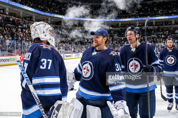 Goaltender Connor Hellebuyck of the Winnipeg Jets gets congratulated by teammates Laurent Brossoit and Tucker Poolman following a 52 victory over the...