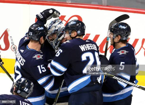 Goaltender Connor Hellebuyck of the Winnipeg Jets gets congratulated by teammates Matt Hendricks Blake Wheeler and Dmitry Kulikov after backstopping...