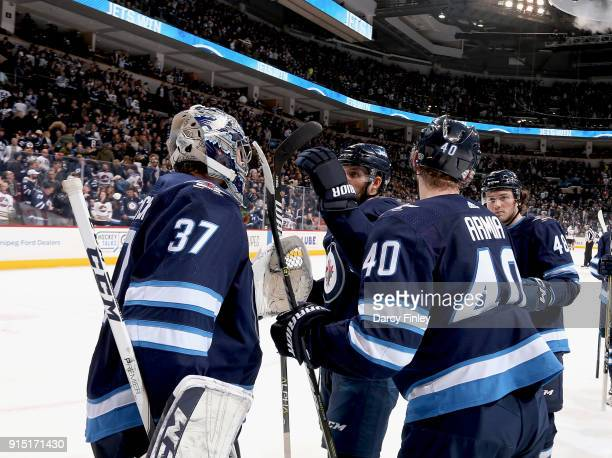Goaltender Connor Hellebuyck of the Winnipeg Jets gets congratulated by teammates Ben Chiarot Joel Armia and Brendan Lemieux following a 43 victory...