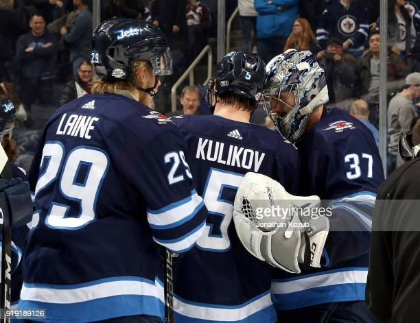 Goaltender Connor Hellebuyck of the Winnipeg Jets gets congratulated by teammates Dmitry Kulikov and Patrik Laine after backstopping the Jets to a 61...