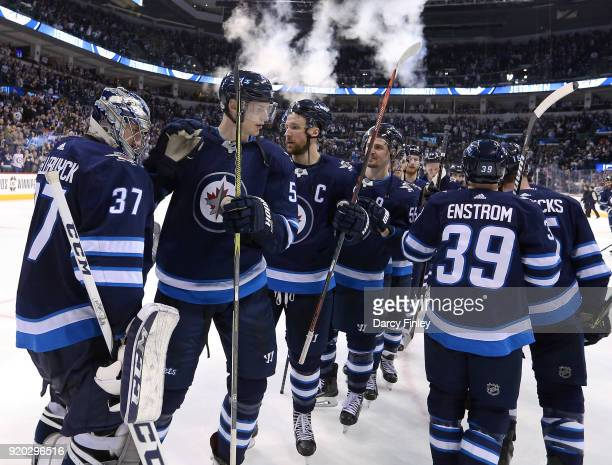 Goaltender Connor Hellebuyck of the Winnipeg Jets gets congratulated by his teammates following a 72 victory over the Florida Panthers at the Bell...