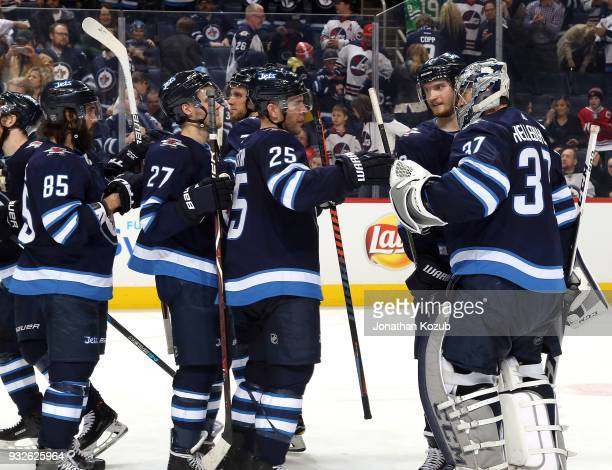Goaltender Connor Hellebuyck of the Winnipeg Jets gets congratulated by teammates following a 62 victory over the Chicago Blackhawks at the Bell MTS...