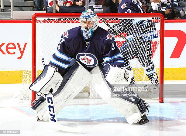 Goaltender Connor Hellebuyck of the Winnipeg Jets gets set in the crease prior to puck drop against the Montreal Canadiens at the MTS Centre on...