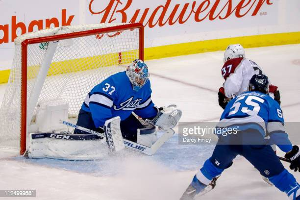 Goaltender Connor Hellebuyck of the Winnipeg Jets guards the net as JT Compher of the Colorado Avalanche carries the puck towards the goal during...
