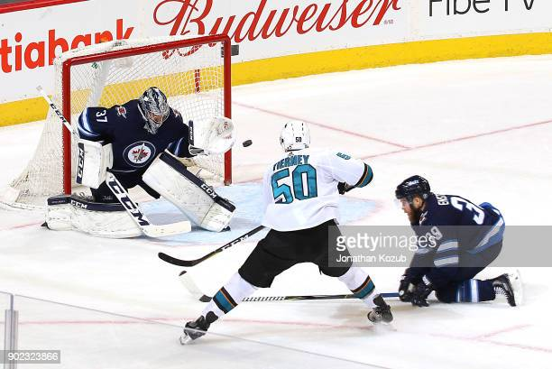 Goaltender Connor Hellebuyck of the Winnipeg Jets guards the net as Chris Tierney of the San Jose Sharks shoots the puck past a defending Toby...