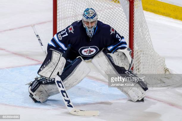 Goaltender Connor Hellebuyck of the Winnipeg Jets guards the net during first period action against the Calgary Flames at the MTS Centre on March 11...