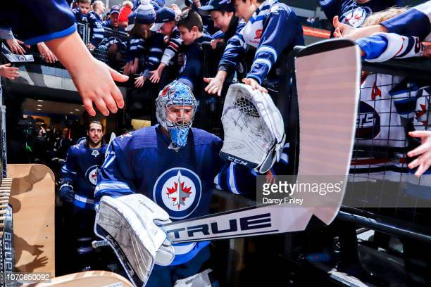 Goaltender Connor Hellebuyck of the Winnipeg Jets heads to the ice for the start of the pregame warm up prior to NHL action against the Philadelphia...