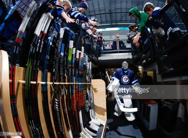 Goaltender Connor Hellebuyck of the Winnipeg Jets heads to the ice for the pregame warm up prior to NHL action against the San Jose Sharks at the...