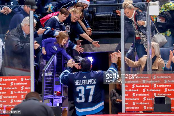Goaltender Connor Hellebuyck of the Winnipeg Jets high fives fans as he leaves the ice after receiving first star honours in a 71 victory over the...