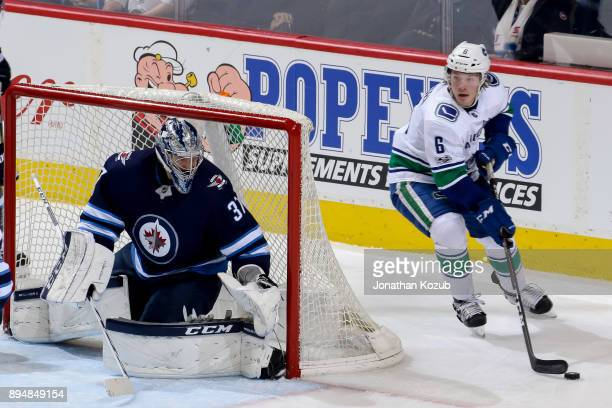 Goaltender Connor Hellebuyck of the Winnipeg Jets keeps an eye on Brock Boeser of the Vancouver Canucks as he plays the puck behind the net during...