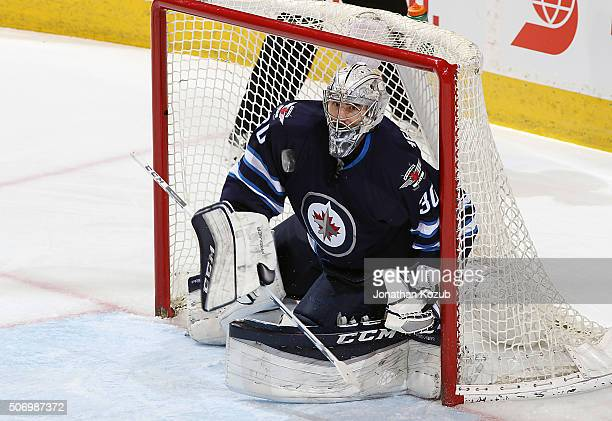 Goaltender Connor Hellebuyck of the Winnipeg Jets keeps his eye on the flying puck during first period action against the Arizona Coyotes at the MTS...