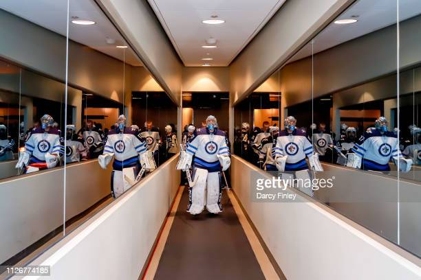 Goaltender Connor Hellebuyck of the Winnipeg Jets leads his teammates to the ice for the start off the pregame warm up prior to NHL action against...