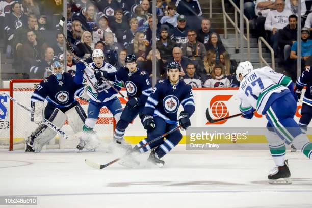 Goaltender Connor Hellebuyck of the Winnipeg Jets looks around a screen as Ben Hutton of the Vancouver Canucks takes a shot off the point during...