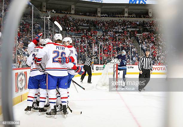 Goaltender Connor Hellebuyck of the Winnipeg Jets looks on as Montreal Canadiens players celebrate a first period goal by Brian Flynn at the MTS...