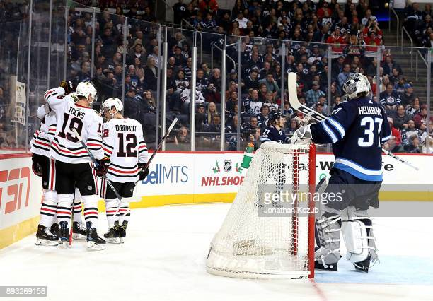 Goaltender Connor Hellebuyck of the Winnipeg Jets looks on as Jonathan Toews and Alex DeBrincat of the Chicago Blackhawks celebrate a third period...