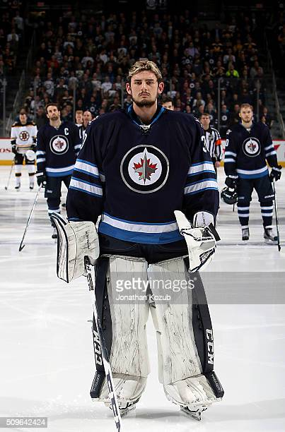 Goaltender Connor Hellebuyck of the Winnipeg Jets looks on during the singing of the National anthems prior to puck drop against the Boston Bruins at...