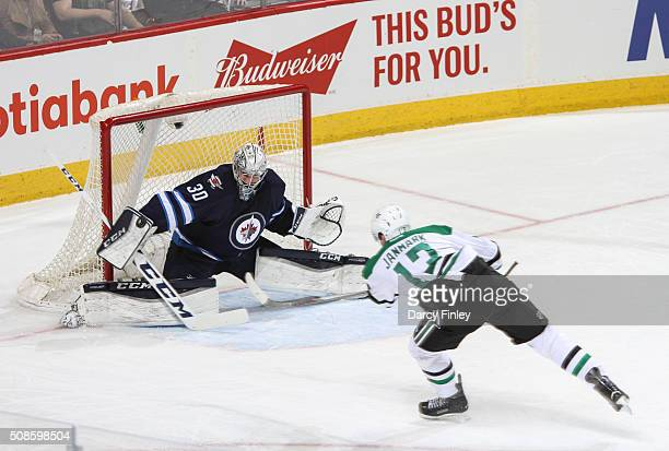 Goaltender Connor Hellebuyck of the Winnipeg Jets makes a blocker save on a shot by Mattias Janmark of the Dallas Stars during second period action...