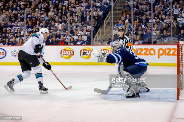 Goaltender Connor Hellebuyck of the Winnipeg Jets makes a glove save on Tomas Hertl of the San Jose Sharks during a third period breakway at the Bell...