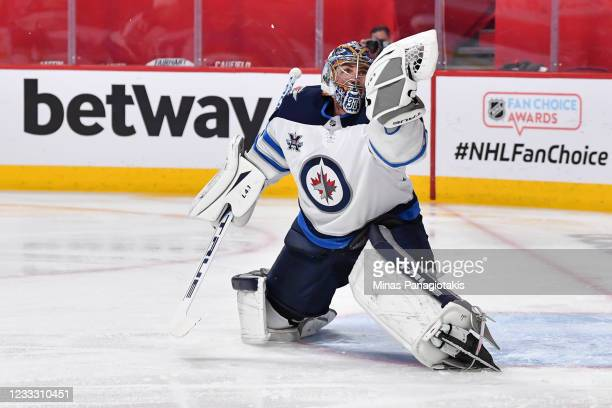 Goaltender Connor Hellebuyck of the Winnipeg Jets makes a glove save against the Montreal Canadiens during the second period in Game Three of the...