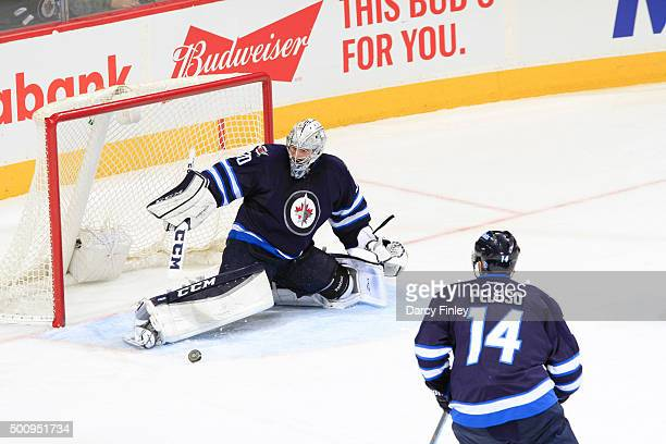 Goaltender Connor Hellebuyck of the Winnipeg Jets makes a pad save as teammate Anthony Peluso looks on during second period action against the...