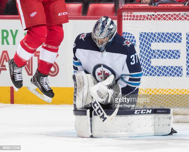 Goaltender Connor Hellebuyck of the Winnipeg Jets makes a save as Anthony Mantha of the Detroit Red Wings jumps in the air during an NHL game at...
