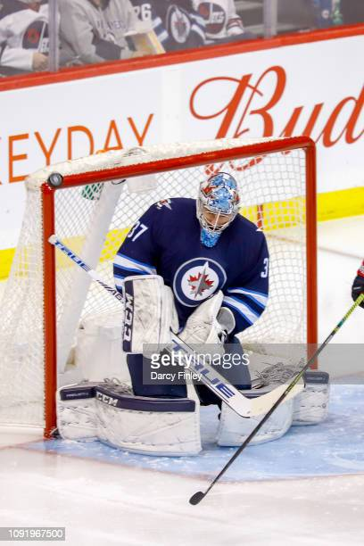 Goaltender Connor Hellebuyck of the Winnipeg Jets makes a save as the puck deflects over the net during second period action against the Columbus...