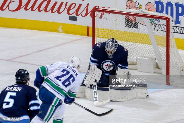 Goaltender Connor Hellebuyck of the Winnipeg Jets makes a save on a shot by Thomas Vanek of the Vancouver Canucks during third period action at the...