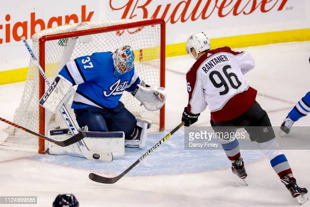 Goaltender Connor Hellebuyck of the Winnipeg Jets makes a stick save on Mikko Rantanen of the Colorado Avalanche during second period action at the...