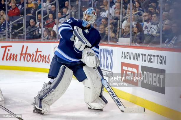 Goaltender Connor Hellebuyck of the Winnipeg Jets plays the puck behind the net during third period action against the Tampa Bay Lightning at the...