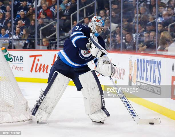 Goaltender Connor Hellebuyck of the Winnipeg Jets plays the puck around the net during third period action against the Dallas Stars at the Bell MTS...