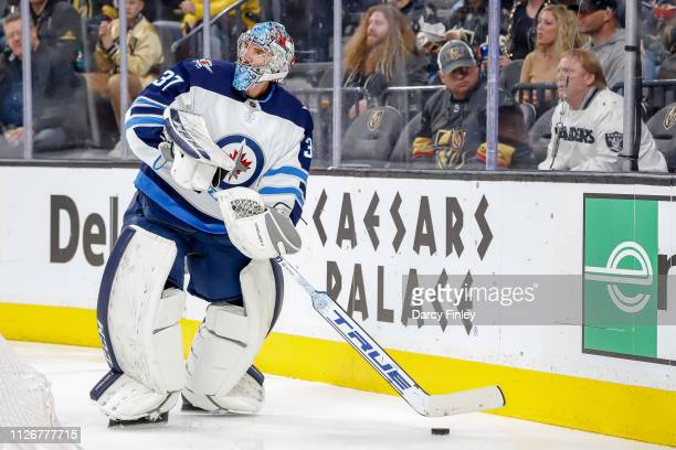 Goaltender Connor Hellebuyck of the Winnipeg Jets plays the puck behind the net during second period action against the Vegas Golden Knights at...